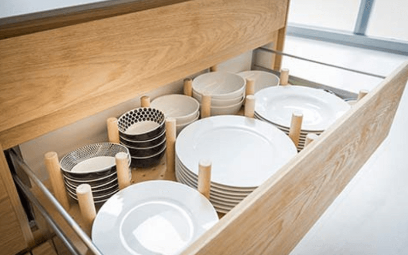 An Organized Dish Drawer Using A Peg System - Image by Queen Bee of Honey Do's