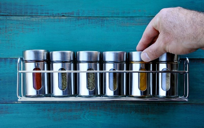 Chef hand returning spice into a spice rack