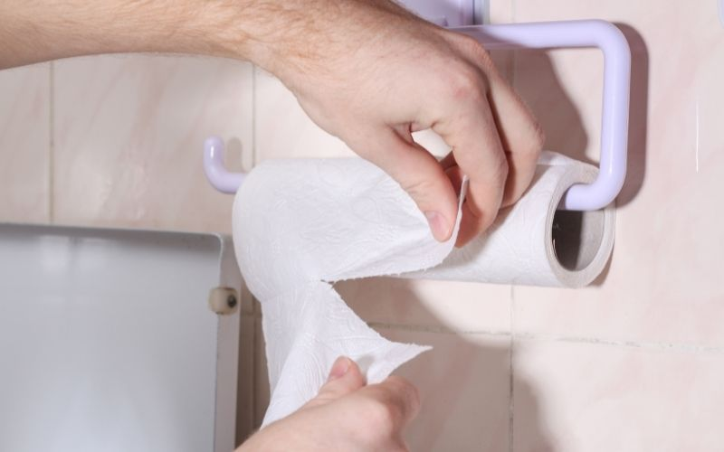 Man tears off a sheet of paper tea towel to dry his hands