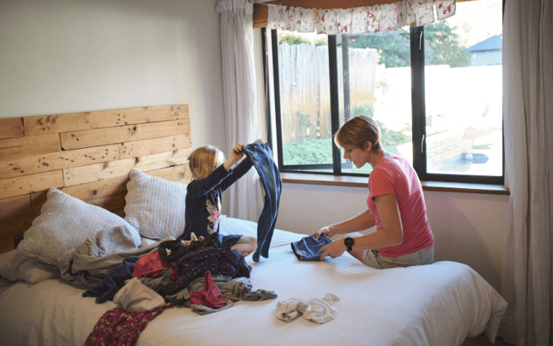 Mother And Son Sorting And Folding Clothes