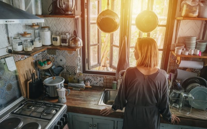 Woman standing next to a window in an old narrow cluttered kitchen