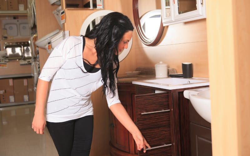 A woman checking out an under sink cabinet.