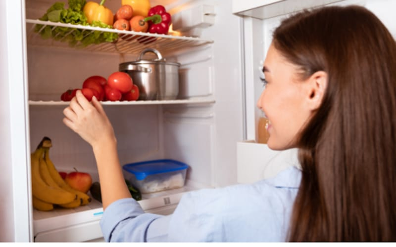 A woman taking fruit from the fridge