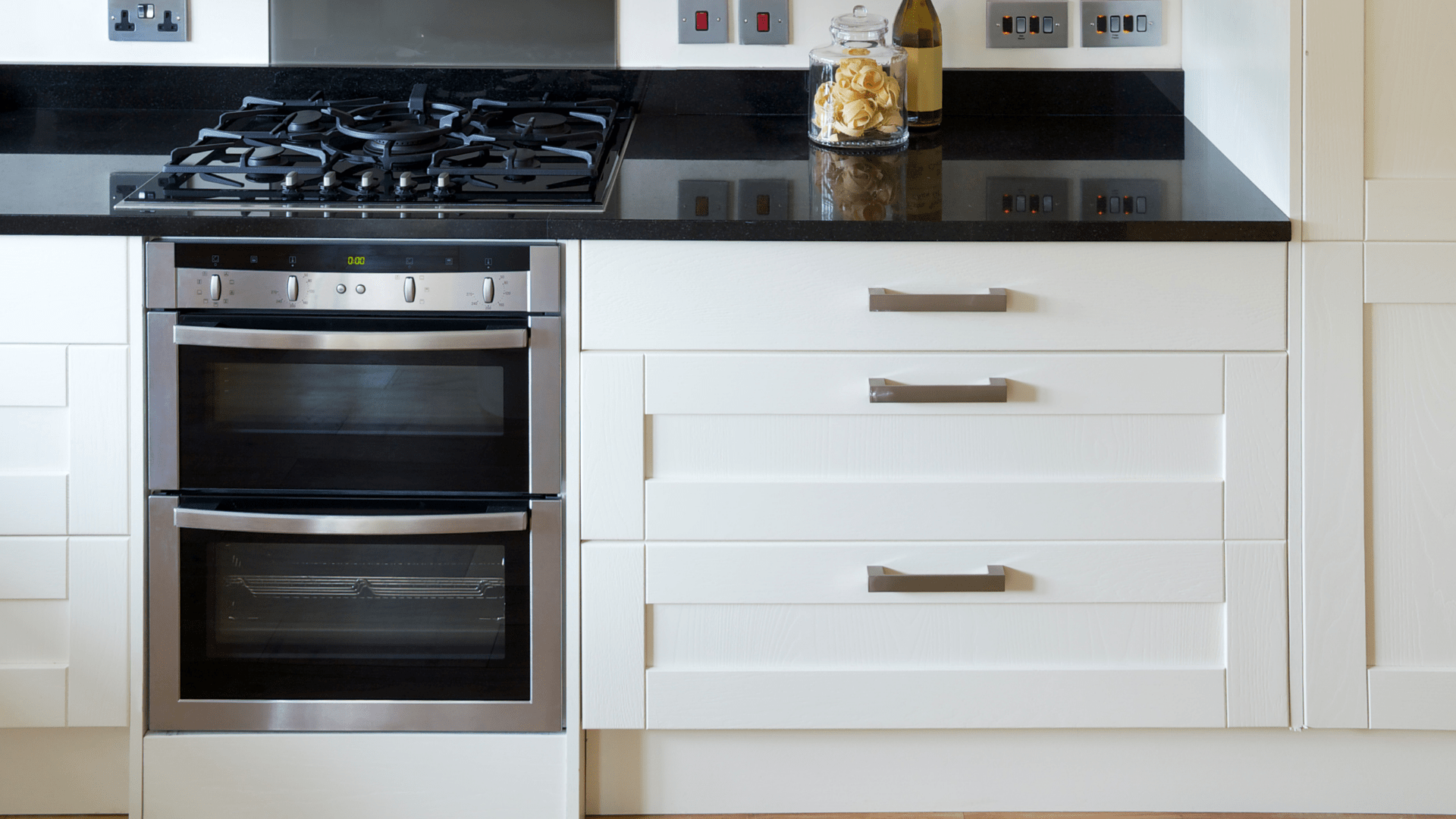 double oven with gas range beside a kitchen drawer