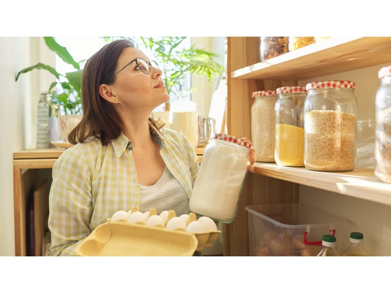 A Woman Looking For Items In Her Pantry