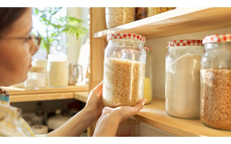 Woman looking at rice in a jar in the pantry
