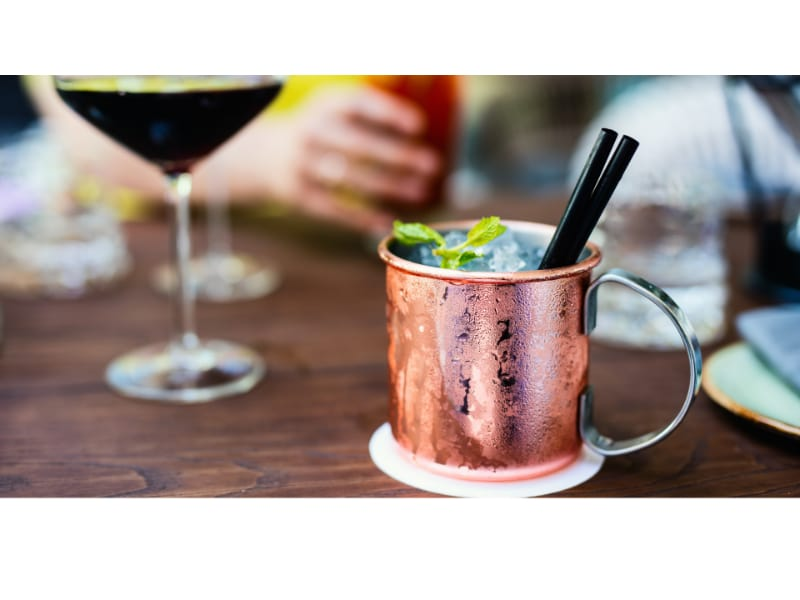 A Moscow Mule on a table with drinks