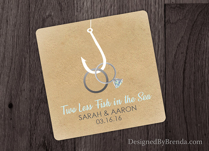 Two Less Fish in the Sea Paper Coaster Wedding Favor - Rings on Hook on Rustic Sandy Background