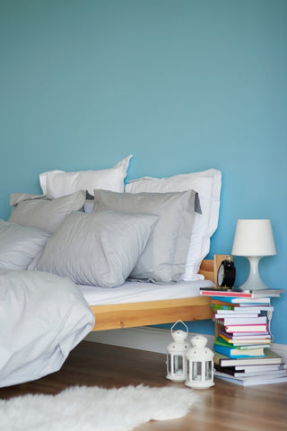 blue wall with a bed in front, white pillows. lamp stand on the right side that look like a pile of books