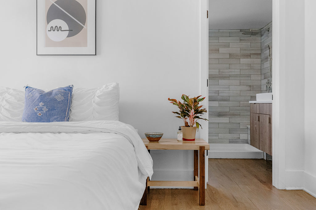 bedroom with bed covered in white blanket, white pillows, and blue pillow