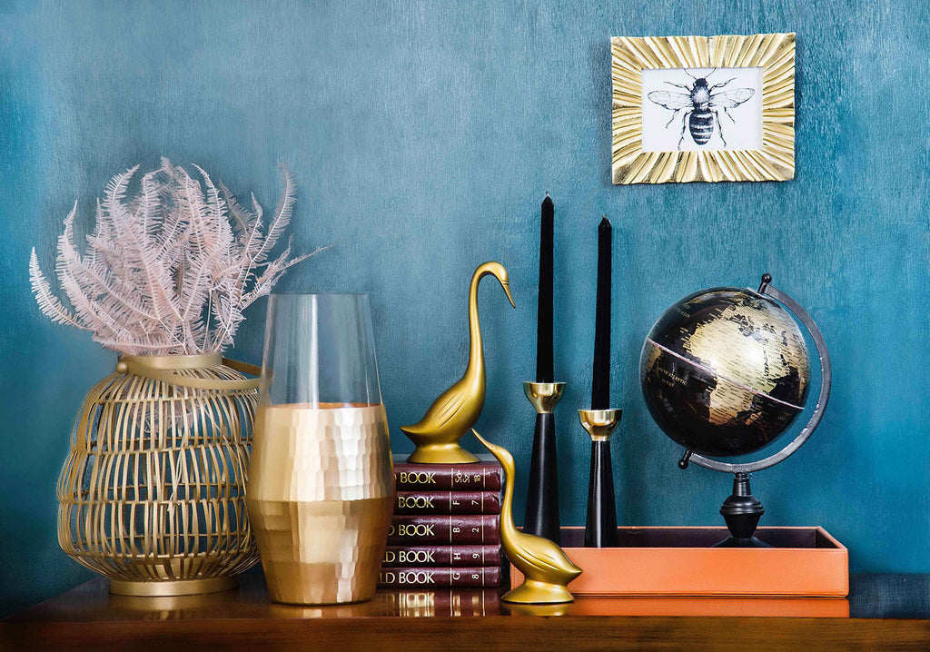 shelf with burgundy books gold bird statues black candles and globe on top with blue wall behind it and illustration of bee hanging on wall