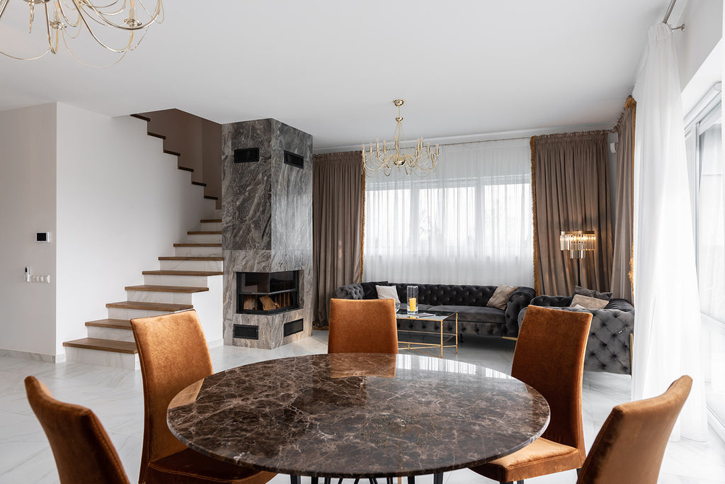 modern room with granite table and windows with beige and white drapery in the background