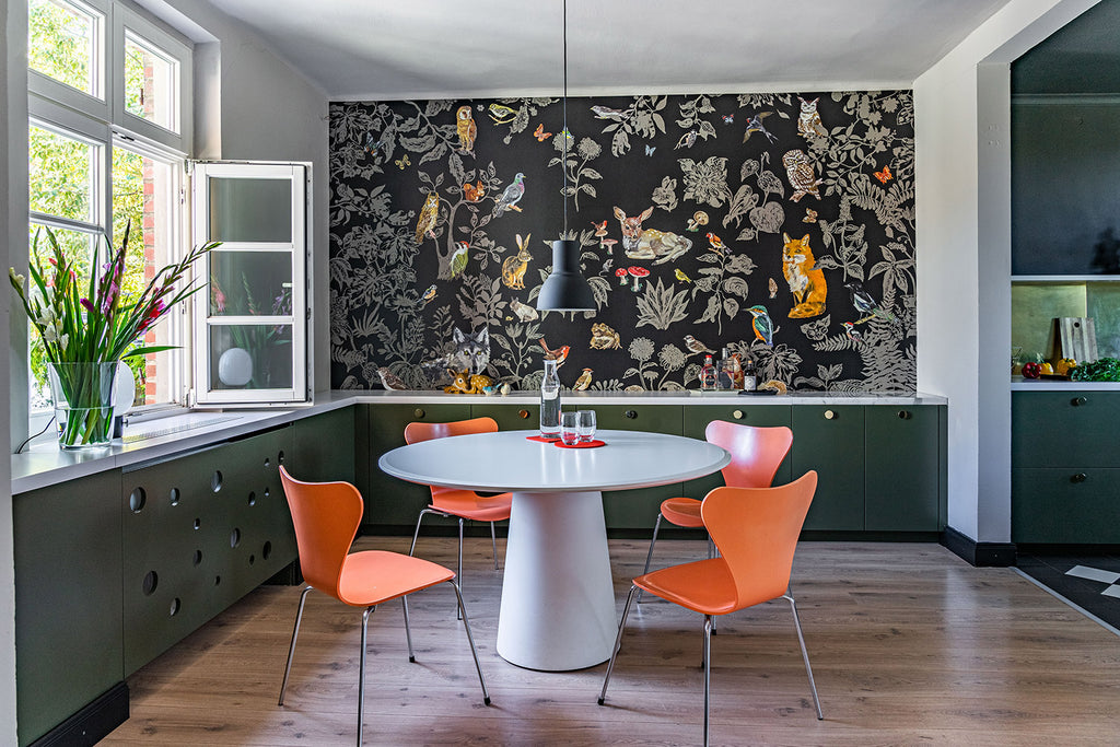 bright room with table surrounded by 4 orange chairs and wall in the background with wallpaper featuring animal illustrations