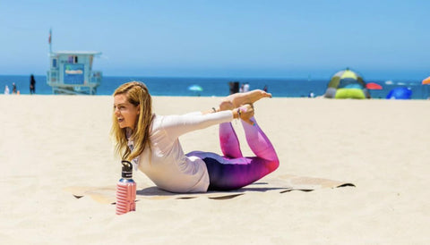Girl playing on the beach with her MOBOT - Sustainable  Foam Roller Water Bottle