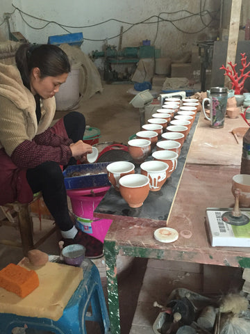After spraying on the glaze there may be some overspray outside of the desired area. Each pot must be inspected and cleaned carefully by hand.
