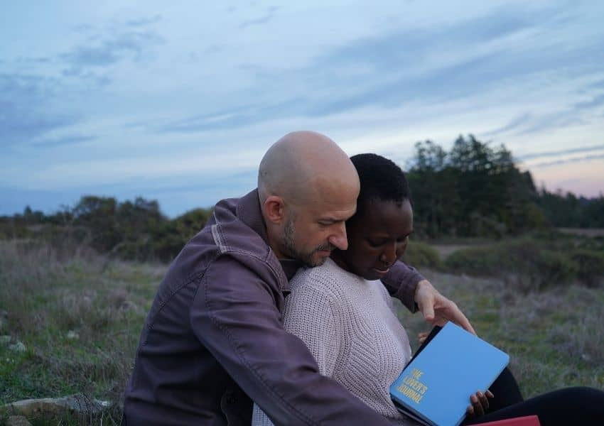 interracial couple sitting in a field