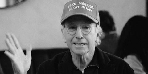 Photograph of Larry David wearing a Make American Great Again cap to make a point