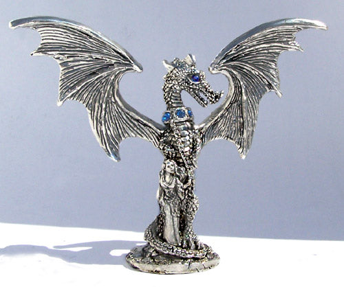 pewter dragon chained with wings spread and feamle holding the dragons chains standing next to the dragon.