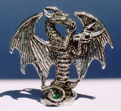 pewter dragon with hand on chin tentatively listening to Dragon skull that he is holding