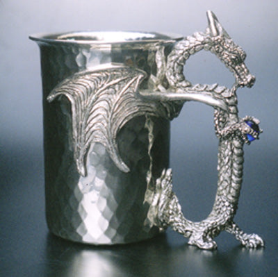 hammered pewter stein with dragon wings wrapped around stein and dragon holding gems as handle