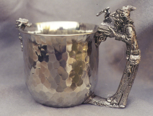 dragn looking inside pewter cup with wizard casting a spelling into the cup for a handle