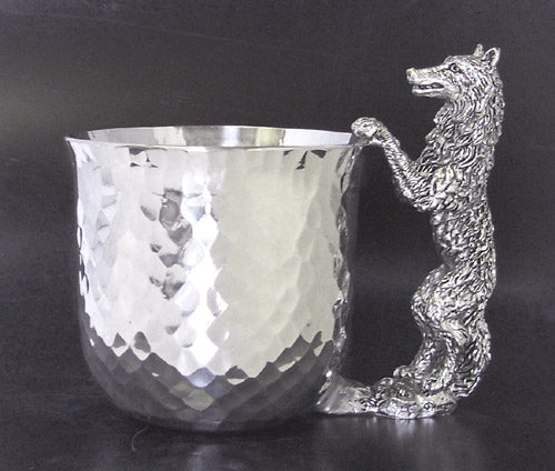 pewter cup with pewter wolf standing and paws on top of cup for handle.