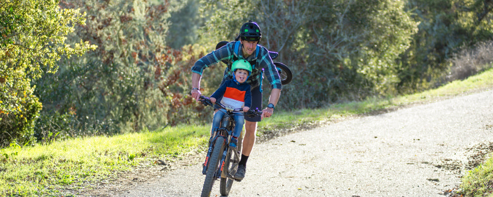 Father and son riding bike on trail