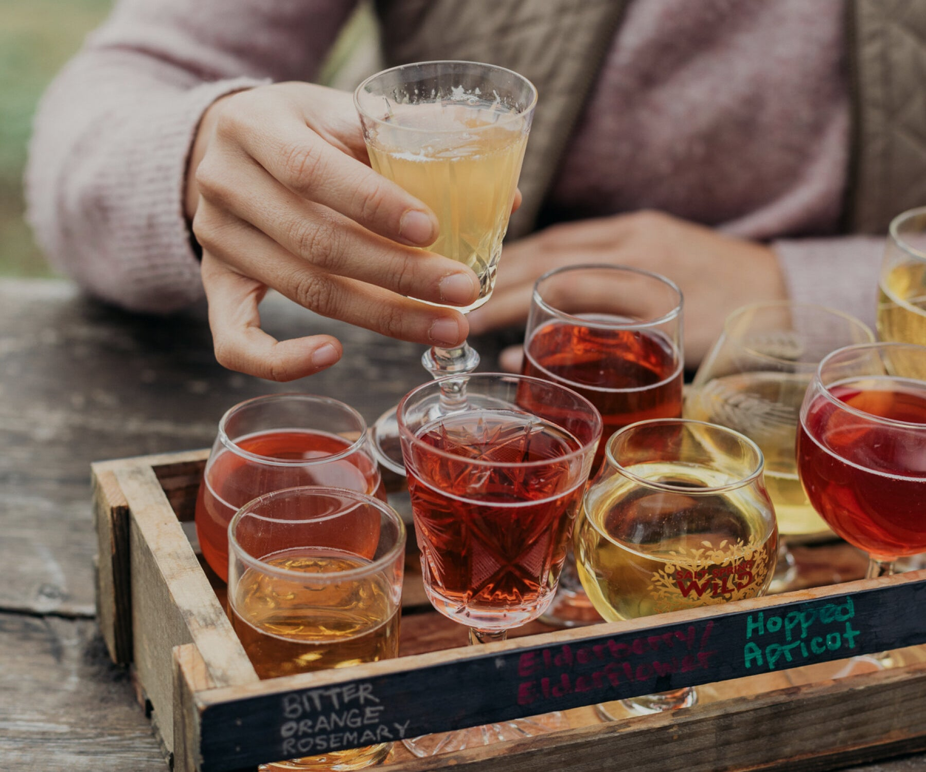 Salt Spring Wild Cider on Salt Spring Island has delicious cider flights, placed in mismatched glassware, pictured is a woman taking one to sip