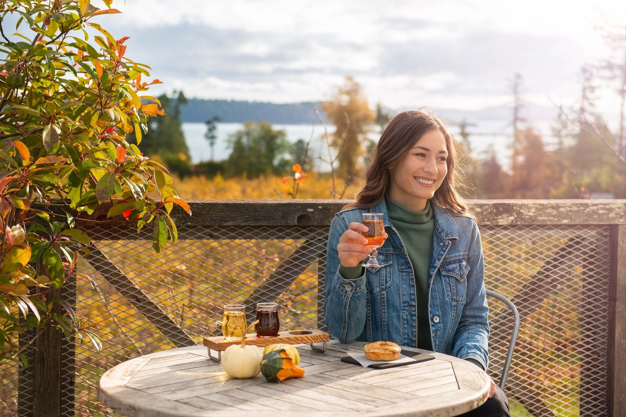 Woman enjoying cider outside on the patio at Sea Cider Farm and Cider House located outside of Victoria, British Coumbia
