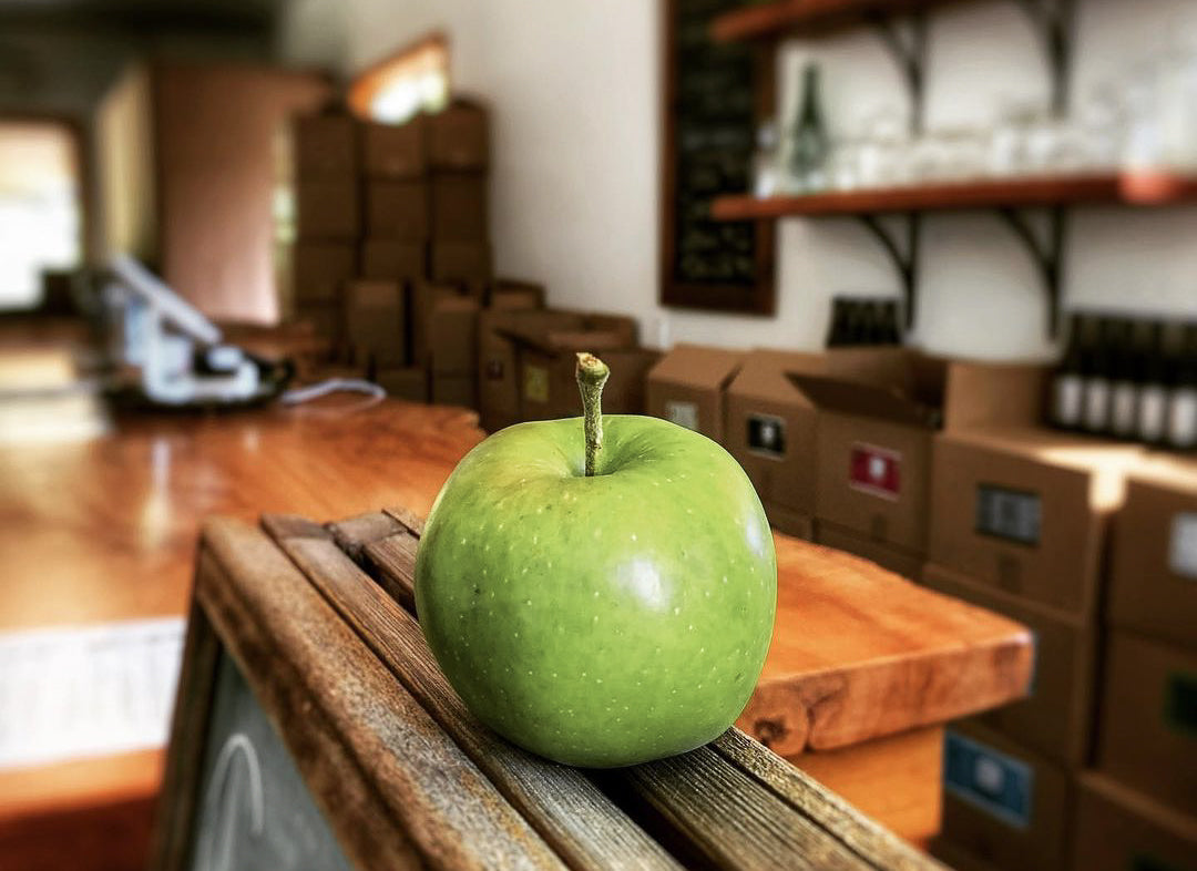 Valley Cider store interior with boxes of ciders lining the walls and a big green apple perched on a chalkboard post