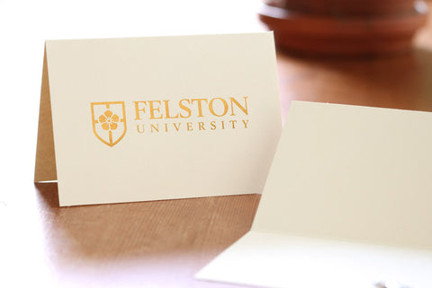 Ivory note card with company logo stamped in gold foil