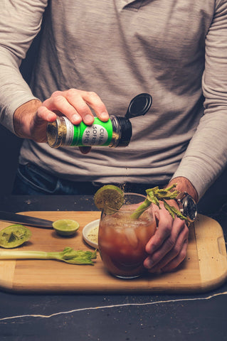 Sprinkling bloody mary with sofrito spice