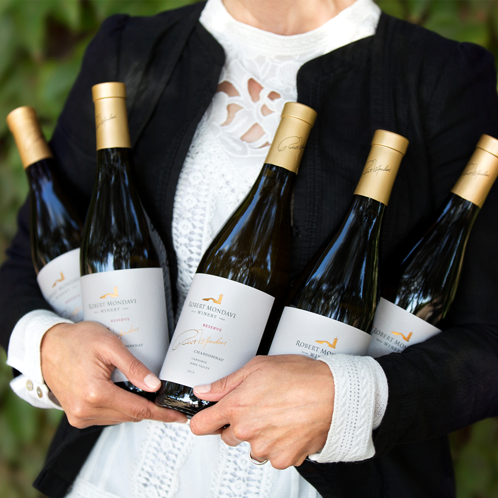 Woman holding several wine bottles in her arms
