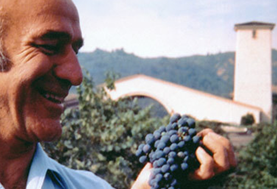 Robert Mondavi smiling at a bunch of red wine grapes with the iconic arch and tower of his winery behind him.