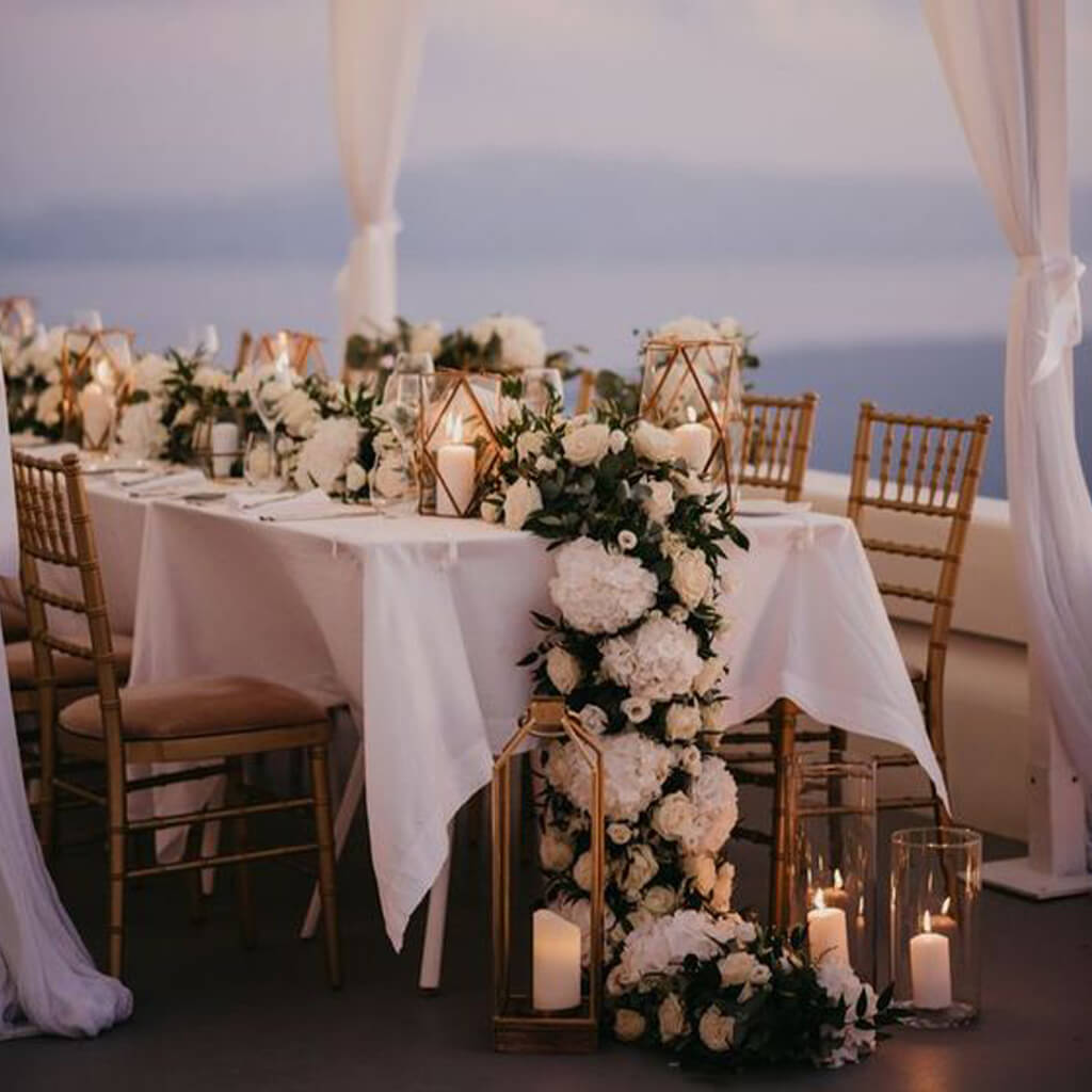 A wedding dinner table filled with flowers and candles