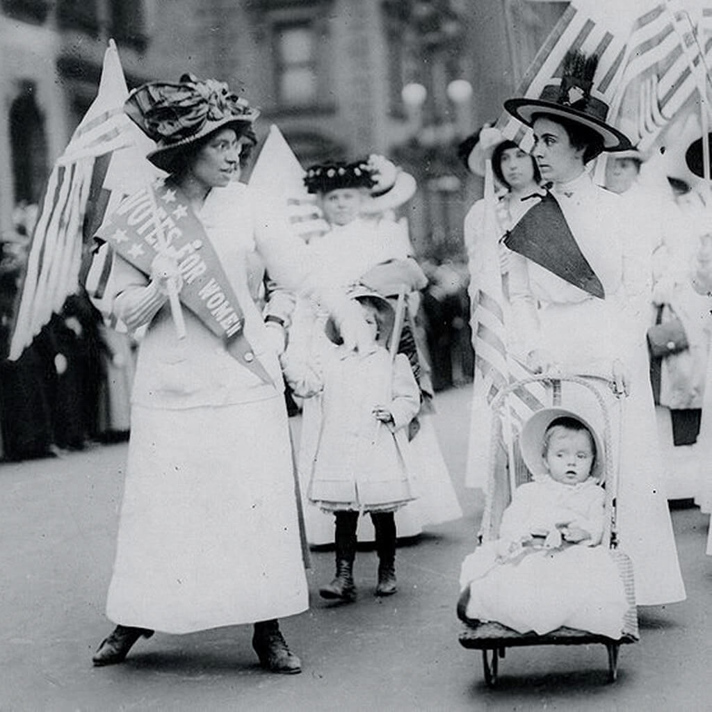 Women wearing white marching with flags