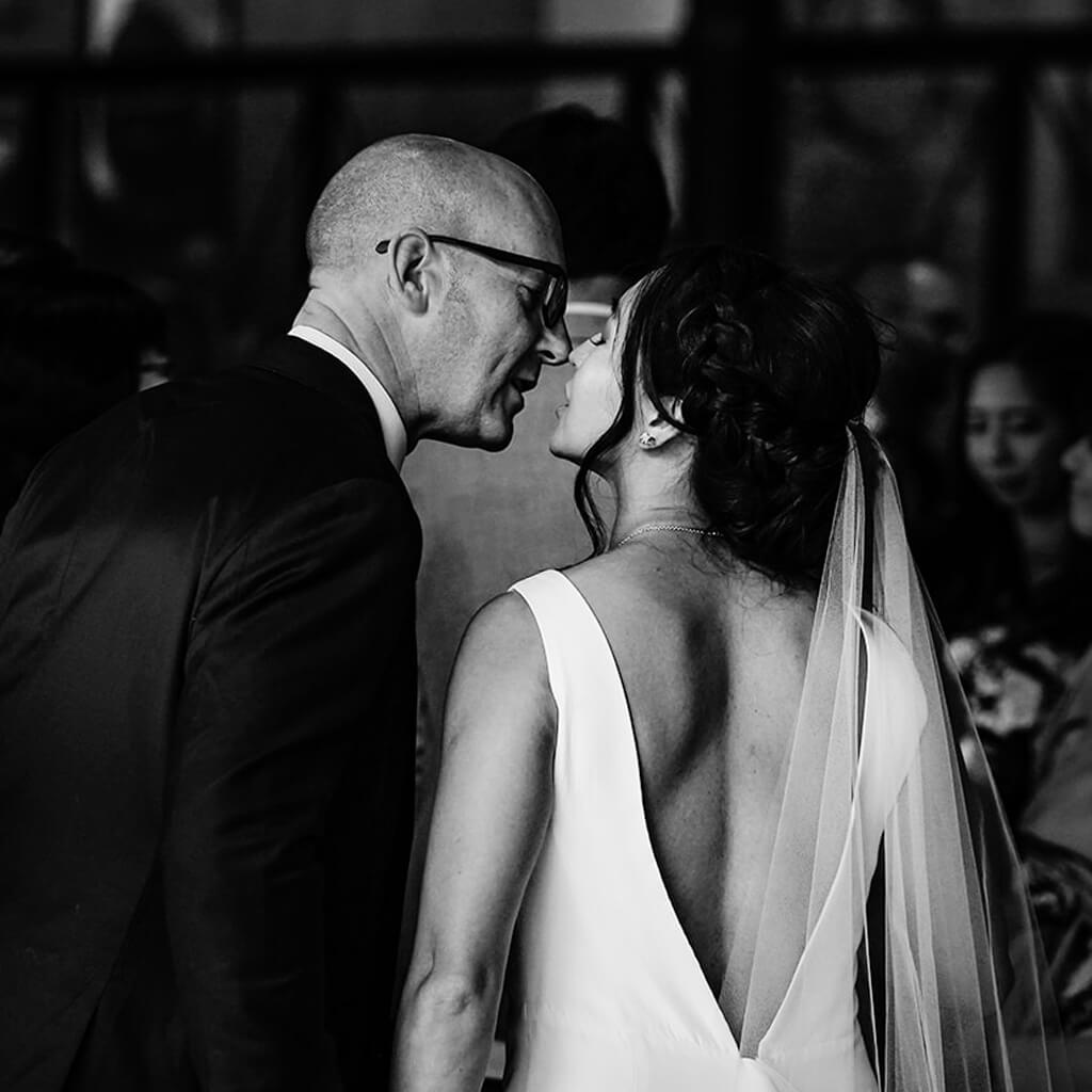 A bride and groom kissing. The bride is wearing Christina Devine wedding dress and veil