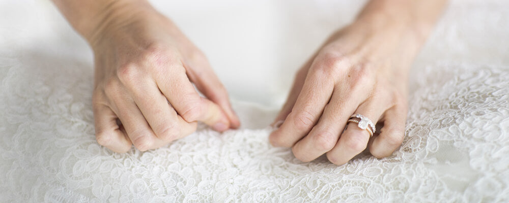 Hands sewing lace fabric inside the Christina Devine studio
