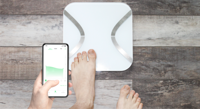 man stepping on korescale holding smartphone with feelfit app open