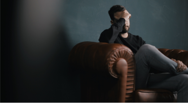 man sitting on couch with his hand over his face, clearly stressed out
