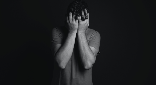 black & white photo of man holding his head in his hands distressed