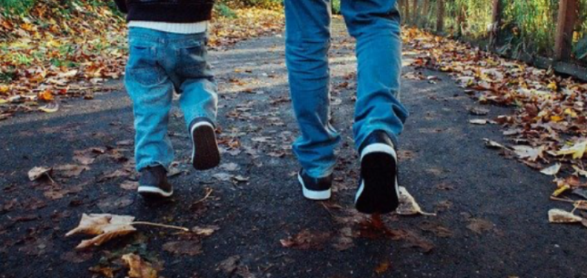 father & son walking together in leaves with matching shoes