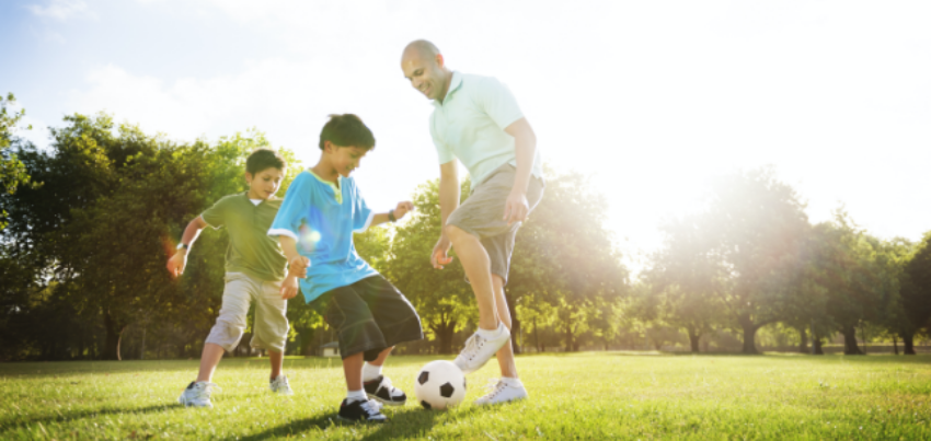 father and sons playing soccer outside