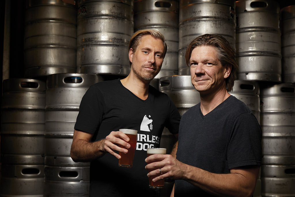 This photo shows Hairless Dog Brewing Company Co-Founders Jeff Hollander, left, and Paul Pirner. Each are holding a pint glass of Hairless Dog NA brew.