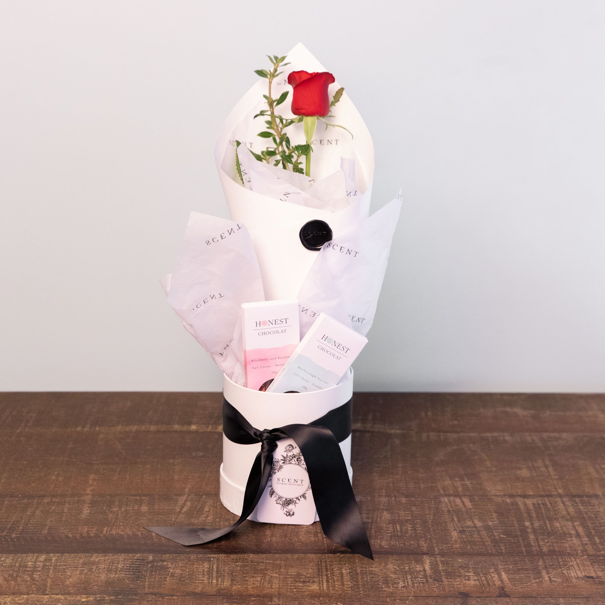 A beautifully wrapped single rose and two mini Honest chocolate bars in a hatbox.