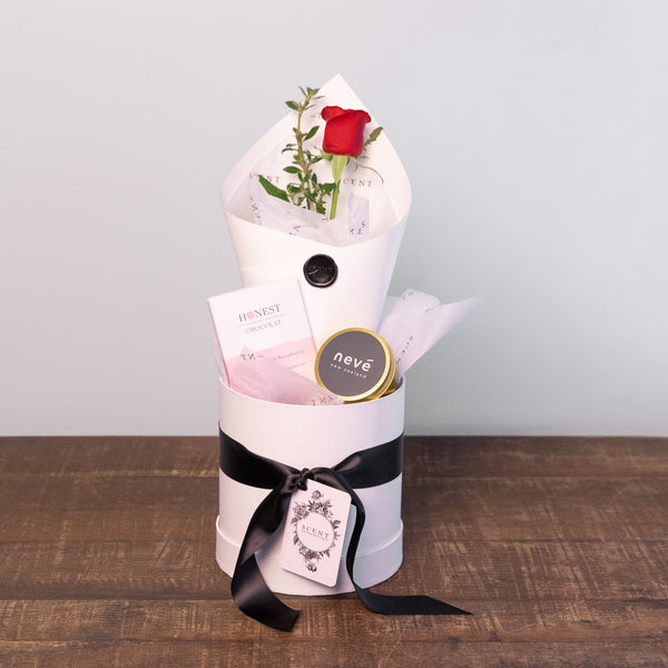 A beautifully wrapped single rose, a large Honest chocolate bar and a mini Neve candle in a hatbox.