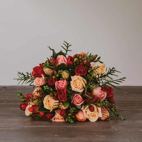A gorgeous posy made up of fresh seasonal New Zealand grown flowers in apricot, peach, orange and red tones