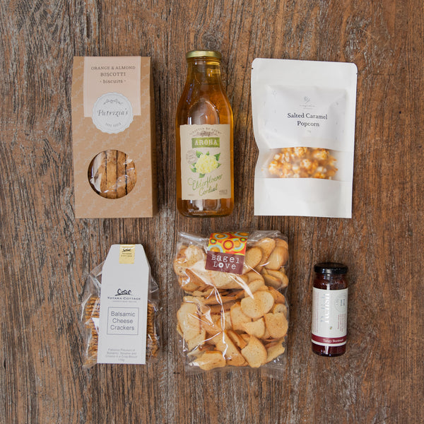 A yummy assortment of snacks that includes bagel crisps, relish, biscotti, crackers, cordial and caramel popcorn.