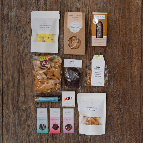 An assortment of yummy sweet and savoury treats that includes caramel popcorn, marshmallow, biscuits, hokey pokey, biscotti, tea, coffee, bagel crisps, crackers and chocolate.