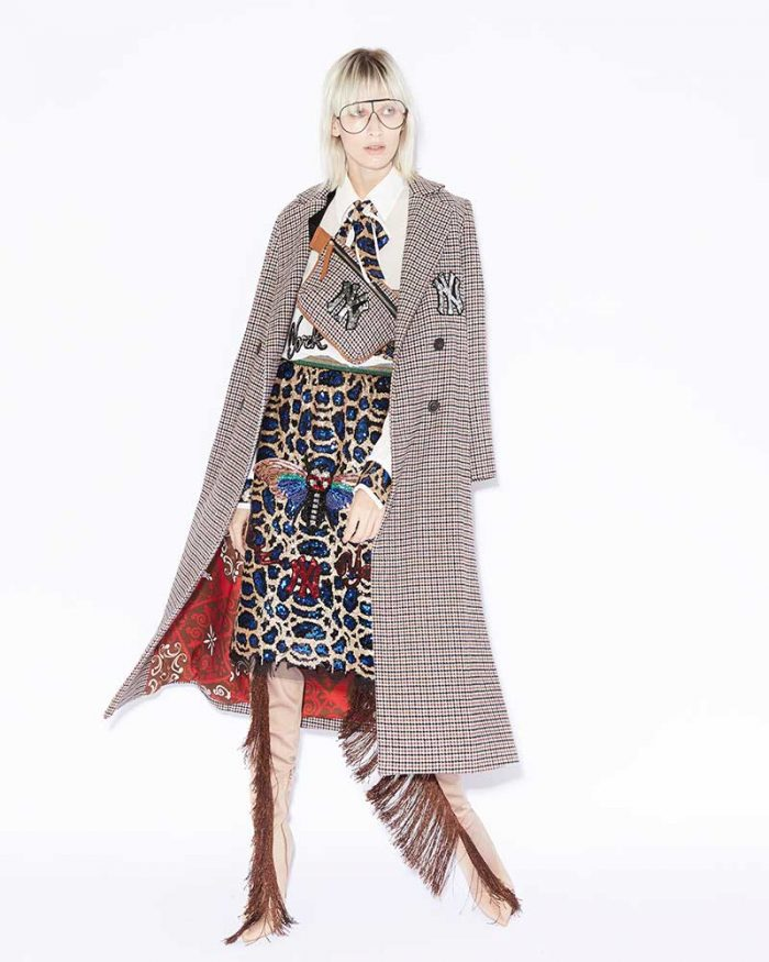 Model wearing total look 5 PROGRESS: tartan coat, white shirt with knotted bow at the neck spotted print in sequins, spotted skirt in sequins, cuissard boots with fringe